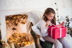 Regalos felices de la Navidad de la abertura de la muchacha por una chimenea adornada en sala de estar ligera acogedora el vísper Imagen de archivo libre de regalías