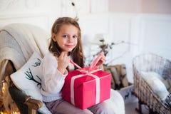 Regalos felices de la Navidad de la abertura de la muchacha por una chimenea adornada en sala de estar ligera acogedora el vísper Fotos de archivo