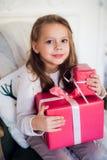 Regalos felices de la Navidad de la abertura de la muchacha por una chimenea adornada en sala de estar ligera acogedora el vísper Foto de archivo libre de regalías