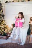 Regalos felices de la Navidad de la abertura de la muchacha por una chimenea adornada en sala de estar ligera acogedora el vísper Foto de archivo