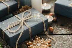 Regalos festivos con las cajas, vela, nieve, conífera, cesta, canela, conos del pino, nueces en fondo de madera Imágenes de archivo libres de regalías