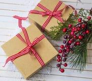 Regalos festivos de la Navidad adornados con la cinta en una tabla de madera Imagen de archivo libre de regalías