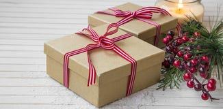 Regalos festivos de la Navidad adornados con la cinta en una tabla de madera Foto de archivo libre de regalías