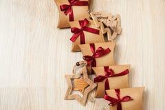 Regalos hechos a mano de la Navidad del documento de Kraft y de los juguetes de madera sobre el árbol de navidad Fotografía de archivo libre de regalías