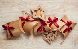 Regalos hechos a mano de la Navidad del documento de Kraft y de los juguetes de madera sobre el árbol de navidad Imagen de archivo libre de regalías