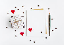 Regalos hechos a mano rústicos y una letra en el fondo blanco adornado con los corazones y los granos de café Visión superior, en Fotografía de archivo