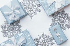 Regalos hermosos de la Navidad y copos de nieve de plata aislados en el fondo blanco Cajas envueltas coloreadas azul en colores p imagen de archivo libre de regalías
