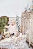 Regalos lindos del bebé y de la Navidad Pequeño niño que se divierte cerca del árbol de navidad en sala de estar Feliz Navidad de foto de archivo