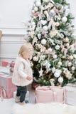 Regalos lindos del bebé y de la Navidad Pequeño niño que se divierte cerca del árbol de navidad en sala de estar Feliz Navidad de fotografía de archivo libre de regalías