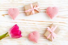 Regalos llenos con la cinta rosada, los corazones hechos punto y el tulipán en un fondo de madera blanco Foto de archivo libre de regalías