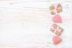 Regalos llenos con la cinta rosada y corazones hechos punto en un fondo de madera blanco Imágenes de archivo libres de regalías
