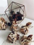 Regalos rústicos en la tabla con el terrario de cristal con los conos del pino Happ Foto de archivo