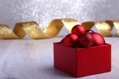 Regalos rojos coloridos con las bolas de la Navidad en el fondo de plata imagenes de archivo