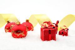 Regalos rojos de la Navidad, cinta de oro de las chucherías en nieve Fotografía de archivo libre de regalías