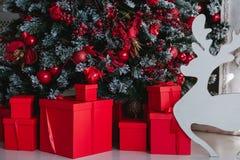Regalos rojos de la Navidad debajo de un árbol de navidad Foto de archivo