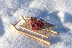Regalos rojos en el trineo en la nieve Fotos de archivo