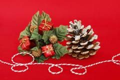 Regalos rojos, hojas del verde y un cono del pino así como un hilo rojo y blanco para adornar los partidos en un fondo rojo fotografía de archivo libre de regalías