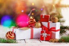 Regalos rojos y blancos del grupo adornado de la Navidad y cascabeles de oro en fondo Tarjeta de felicitación del día de fiesta Imagenes de archivo