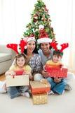 Regalos sonrientes de la Navidad de la apertura de la familia Imágenes de archivo libres de regalías