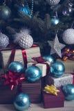 Regalos y chucherías debajo de un árbol de navidad adornado Imagen de archivo libre de regalías