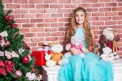 Regalos y concepto de la Navidad El blonde de pelo largo adolescente se sienta en un nightstand blanco cerca del árbol de navidad Foto de archivo libre de regalías