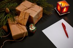 Regalos y cuaderno de la Navidad que mienten cerca de rama spruce verde en la opinión superior del fondo negro Espacio para el te Imagenes de archivo