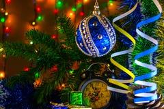 Regalos y reloj de la Navidad con la Navidad y el juguete en una rama de árbol en la guirnalda del fondo Fotos de archivo libres de regalías