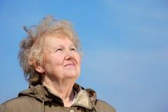 Regard âgé de sourire de femme en ciel Image stock
