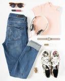 Regard élégant de femme Équipement de femme/fille sur le fond blanc Jeans bleus de denim, T-shirt de pêche, espadrilles d'impress Photographie stock