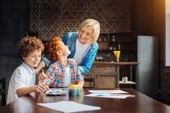 Regard affectueux et petits-enfants de mamie peignant ensemble Image stock
