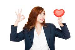 Regard asiatique de signe d'OK d'exposition de femme d'affaires à un coeur Images libres de droits