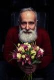 Regard avec du charme d'homme barbu avec un bouquet des tulipes a Image libre de droits