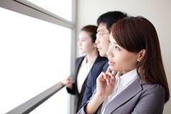 Regard d'équipe d'affaires par la fenêtre Photos stock