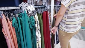 Regard d'achats de femme au-dessus des robes sur des cintres banque de vidéos