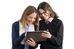 Regard d'amies d'école au comprimé Des adolescentes dans l'uniforme scolaire sur le fond blanc, photo est isolées Photographie stock libre de droits