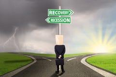 Regard d'entrepreneur à l'enseigne avec des mots de récession de relance Images stock