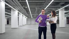 Regard d'homme et de femme aux documents tout en discutant le projet architectural banque de vidéos