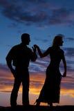 Regard de coucher du soleil de mains de prise de copule de silhouette loin Image stock