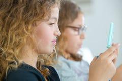 Regard de deux filles au téléphone Images libres de droits