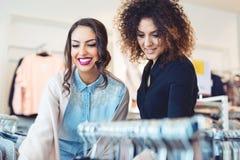 Regard de deux jeunes filles à l'habillement dans le magasin Photo libre de droits