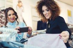 Regard de deux jeunes filles à l'habillement dans le magasin Photo stock