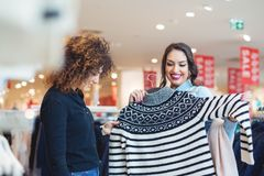 Regard de deux jeunes filles à l'habillement dans le magasin Image stock