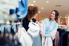 Regard de deux jeunes filles à l'habillement dans le magasin Photos stock