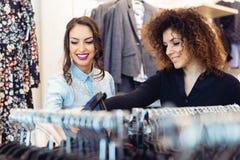 Regard de deux jeunes filles à l'habillement dans le magasin Images stock