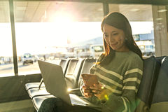 Regard de femme au téléphone portable avec son ordinateur portable à l'aéroport Images libres de droits