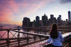 Regard de fille aux bâtiments de Manhattan de Brooklin Bridge à l'aube Images stock