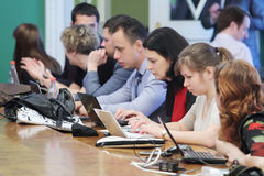 Regard de journalistes aux ordinateurs portables sur la réunion agrandie Images stock