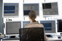 regard de l'opérateur en bourse multiple de moniteurs Photo stock