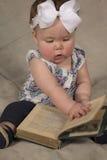 Regard de livre de lecture de bébé vers le bas photo libre de droits