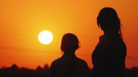 Regard de maman et de fille au beau coucher du soleil au-dessus de la ville et du ciel orange ensemble photographie stock